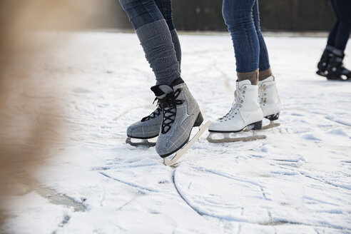Feet of ice skating people on frozen lake - MFF03543