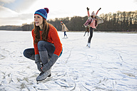 Woman tying her ice skates on frozen lake - MFF03546