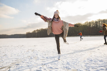 Woman dancing with ice skates on frozen lake with friends - MFF03549