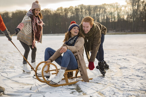 Friends having fun with sledge on frozen lake - MFF03552