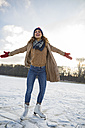 Woman listening to music and ice skating on frozen lake - MFF03558