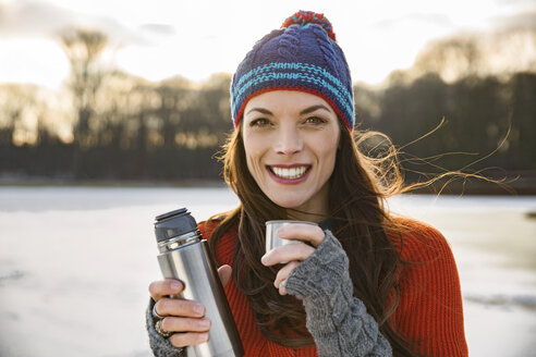 Portrait of smiling woman drinking hot beverage from thermos flask outdoors in winter - MFF03561