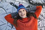 Portrait of happy woman lying down on frozen lake surface - MFF03564