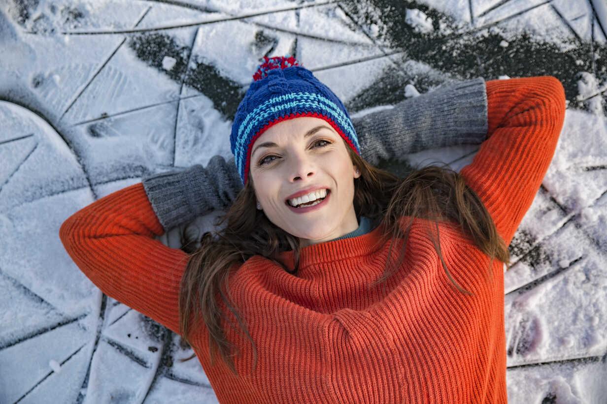 Portrait of happy woman lying down on frozen lake surface - MFF03564 - Mareen Fischinger/Westend61