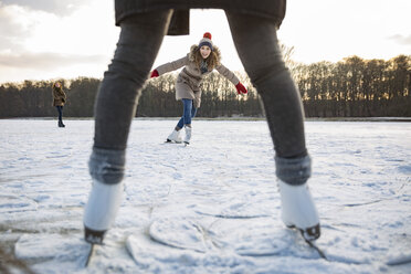Woman ice skating on frozen lake with friends - MFF03567