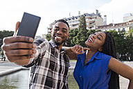 Portrait of happy young couple taking selfie with cell phone - ABZF02029