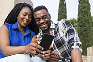 Portrait of smiling young couple looking at cell phone - ABZF02032