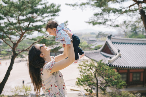 South Korea, Seoul, Happy mother and baby girl playing in Changdeokgung Palace and Huwon - GEMF01637