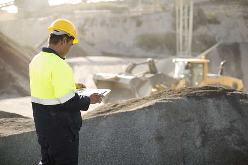Worker standing at quarry, using clipboard - ZEF13733