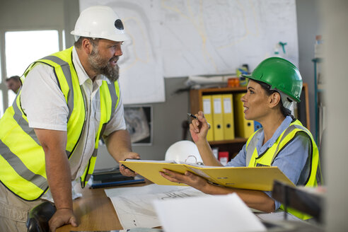 Female quarry worker checking files in office - ZEF13748