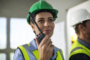 Female quarry worker standing in site office talking on radio device - ZEF13754