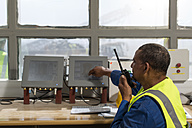 Worker at site office talking at radio device - ZEF13757