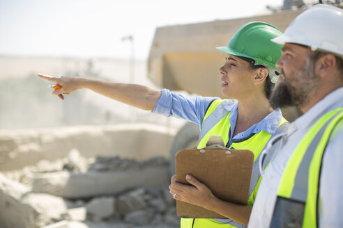 Male and female quarry workers discussing on site - ZEF13760