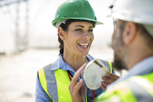 Male and female quarry workers discussing on site - ZEF13763