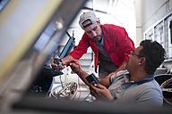 Mechanics restoring vintage cars in workshop - ZEF13805