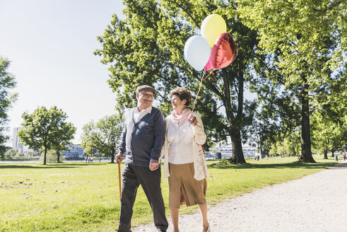 Happy senior couple with balloons strolling in a park - UUF10643
