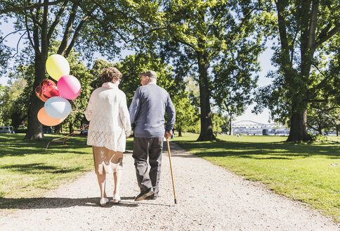 Back view of senior couple with balloons strolling in a park - UUF10646