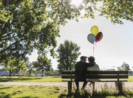 Happy senior couple with balloons sitting on bench in a park - UUF10649