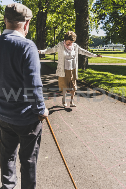 Senior woman playing hopscotch while husband watching her - UUF10652 - Uwe Umstätter/Westend61