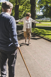 Senior woman playing hopscotch while husband watching her - UUF10652