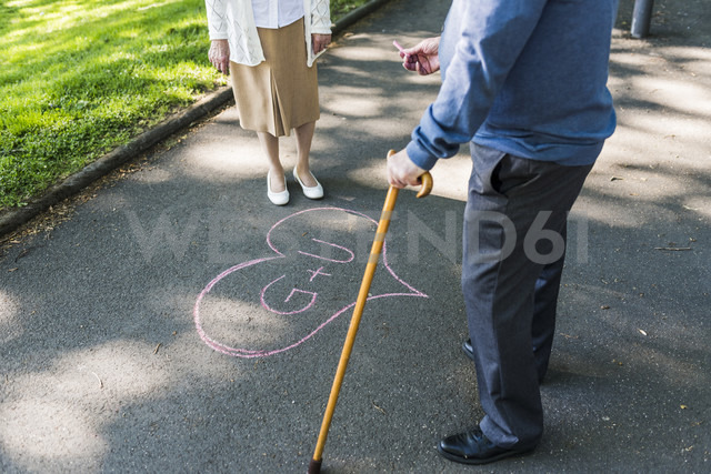 Senior couple drawing love heart with initials on tarmac - UUF10655