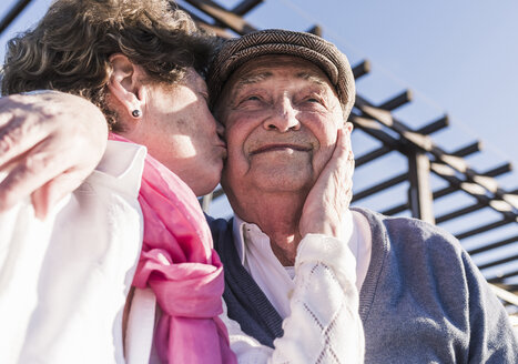 Portrait of happy senior man kissed by his wife - UUF10658