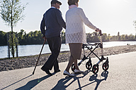 Happy senior couple strolling near river - UUF10661