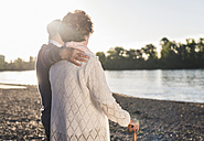 Back view of senior couple at riverside by sunset - UUF10673