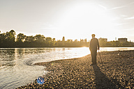 Back view of senior man standing at riverside watching sunset - UUF10676