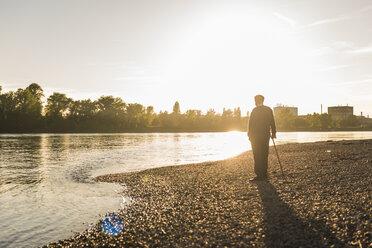Back view of senior man standing at riverside watching sunset - UUF10676