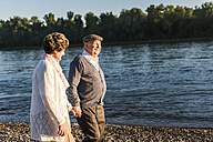 Happy senior couple walking hand in hand at riverside - UUF10682