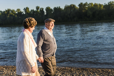 Happy senior couple walking hand in hand at riverside - UUF10682