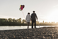 Back view of senior couple with balloons strolling at riverside in the evening - UUF10685