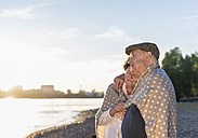 Senior couple relaxing on the beach at sunset - UUF10688