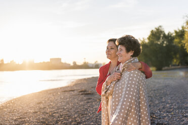 Happy senior woman standing with her adult daughter on the beach at sunset - UUF10691