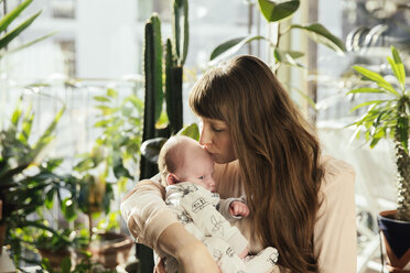 Mother kissing her newborn baby boy at home - MFF03569