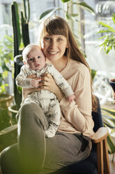 Mother holding her newborn baby boy at home - MFF03572