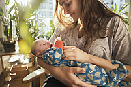 Mother caressing her newborn baby boy at home - MFF03578