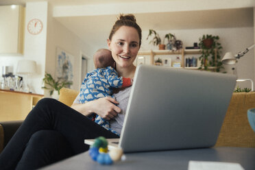 Mother using laptop and holding her newborn baby at home - MFF03581
