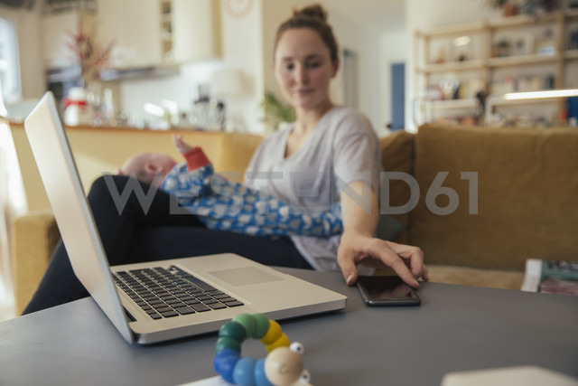 Mother with newborn baby at home taking cell phone from table - MFF03584