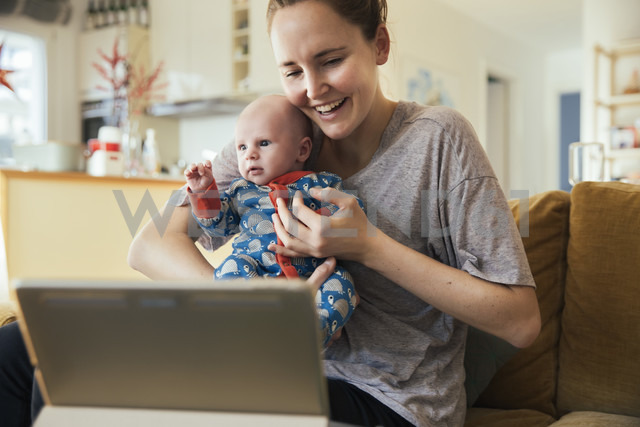 Mother and newborn baby taking a video call at home - MFF03587