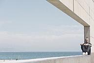 Man with eyes closed sitting on wall near the beach - SKCF00304