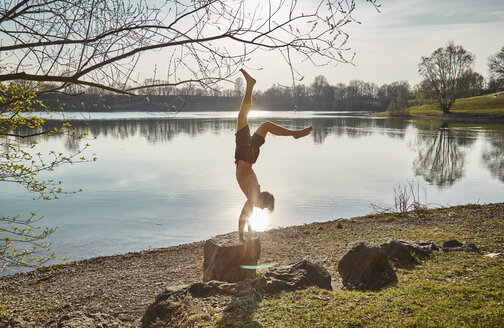 Germany, Bavaria, Feldkirchen, man doing a handstand at lakeshore - KDF00738