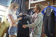 Happy couple shopping for wetsuit in shop - ZEF13845