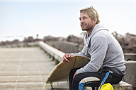 Man sitting with surfboard at the beach - ZEF13851