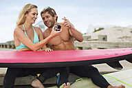 Happy couple with surfboard and camera talking on the beach - ZEF13863