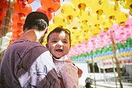 South Korea, Gyeongju, father with a baby girl under colorful paper lanterns at Bulguksa Temple - GEMF01647