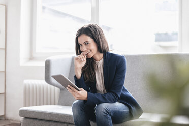Portrait of smiling businesswoman with tablet on couch - JOSF00957