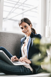 Portrait of smiling businesswoman using laptop on couch - JOSF00966