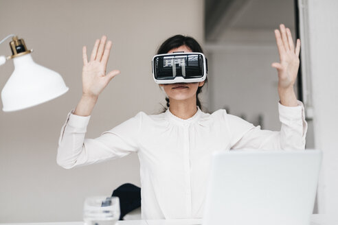 Businesswoman wearing VR glasses in office - JOSF00975